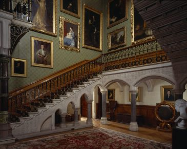 The Main Staircase at Tyntesfield, viewed North West across the Hall, with a carved iron work banister and arched stone supports and family portraits on the walls. Only available as a scan.
